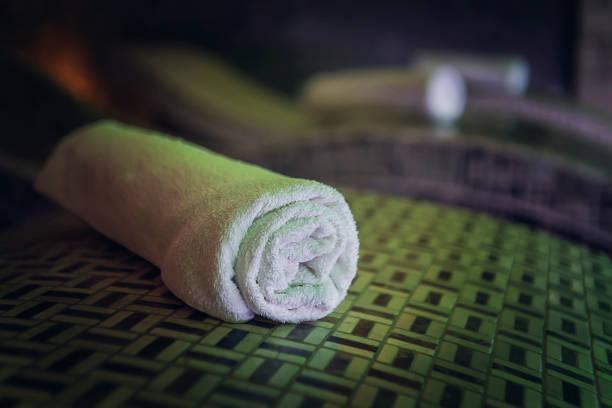 ein nahtauftisch eines baumwollbade-handtuch auf dem holzbettstein in einem luxuriösen spa. saubere und frische einzelschuhe werden sorgfältig auf den saunabeseigen aufgereiht. ein zoom eines handtuchs auf einem zedernbad. - sauna textilien stock-fotos und bilder