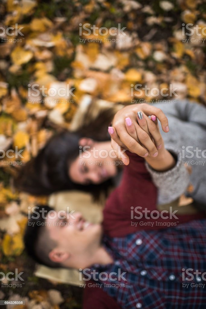 Close up of a couple holding hands in autumn. stock photo