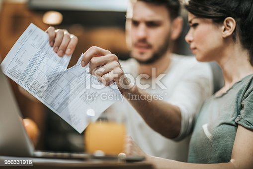 istock Close up of a couple tearing their financial bill at home. 956331916