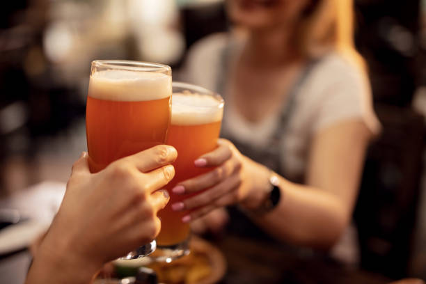 close up of a couple toasting with beer in a pub. - bar zdjęcia i obrazy z banku zdjęć