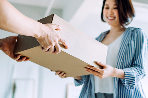 Close up of a courier person making a delivery to a customer at home. Providing a swift express delivery straight into customer's hands