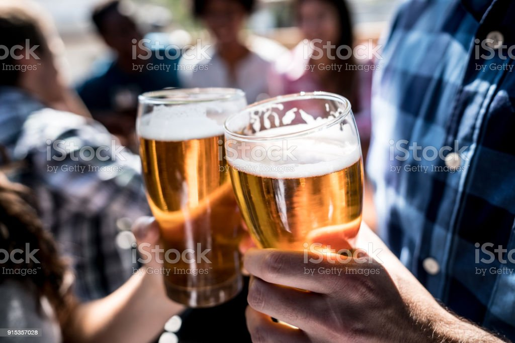 Close up of a customers at a bar holding a beer and making a toast stock photo