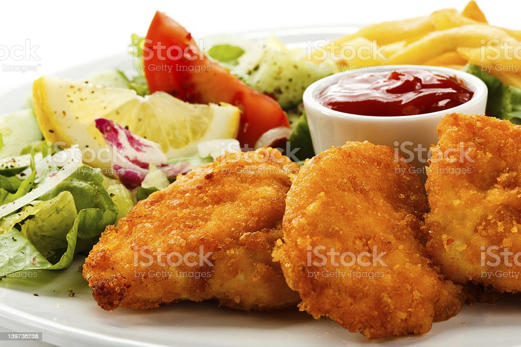 Close up of a dinner with chicken nuggets salad and fries stock photo