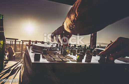 Close up of unrecognizable DJ playing music on turntable during summer beach party at sunset.