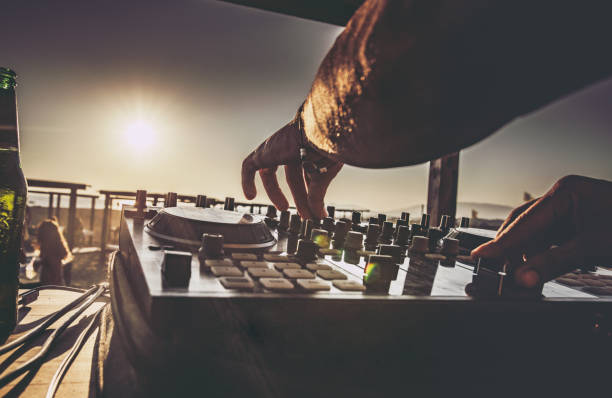 Close up of a DJ playing music on the beach at sunset. Close up of unrecognizable DJ playing music on turntable during summer beach party at sunset. dj stock pictures, royalty-free photos & images