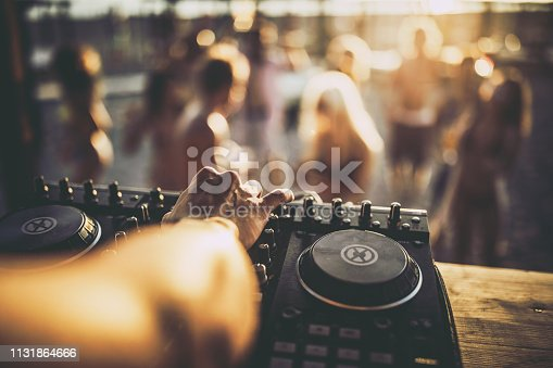Close up of unrecognizable DJ playing music on turntable during summer beach party.