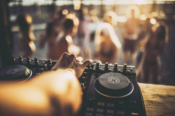 Close up of a DJ playing music on the beach party. Close up of unrecognizable DJ playing music on turntable during summer beach party. dj stock pictures, royalty-free photos & images