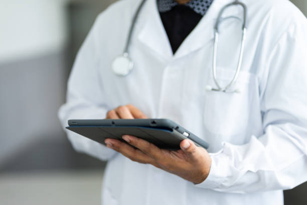 Close up of a doctor checking patient information via tablet. stock photo