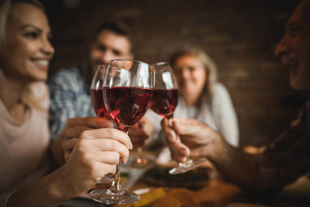 close up of a family toasting with red wine at home. - honour stock photos and pictures