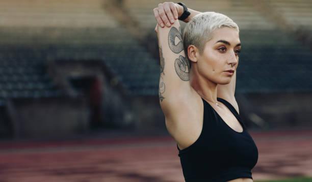 großaufnahme eines weiblichen athleten tun aufwärmübungen - laufende tattoos stock-fotos und bilder