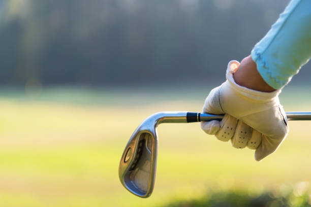 close up of a female golfer holding an iron behind his body - female golfer stock photos and pictures