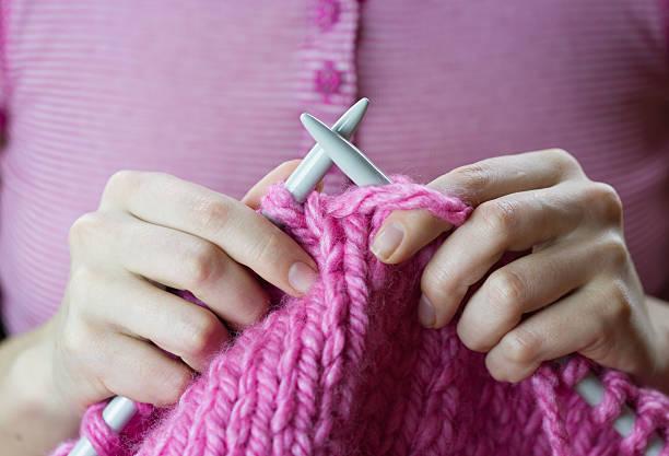 primo piano di donna le mani di lavorazione a maglia filato rosa woolen - lavorare a maglia foto e immagini stock