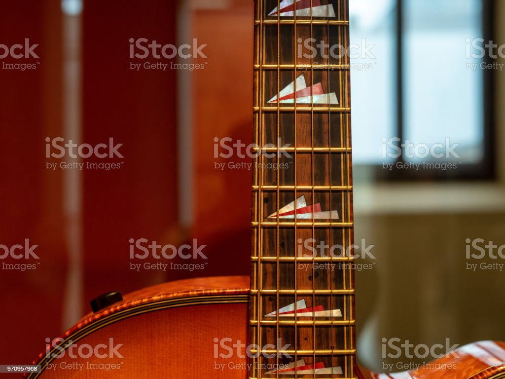 Close Up Of A Fingerboards Stings On An Acoustic Guitar With Dark
