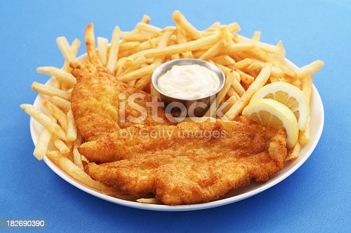 Full-frame, high-resolution digital capture of a plate of delicious, crispy fried fish and chips with a metal ramekin of tartar sauce. Plate sits on a blue surface, and is garnished with lemon slices.