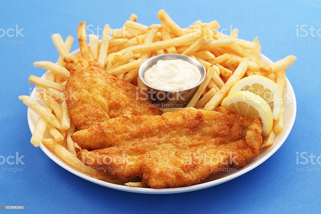 A close up of a fish and chips platter with dipping sauce stock photo