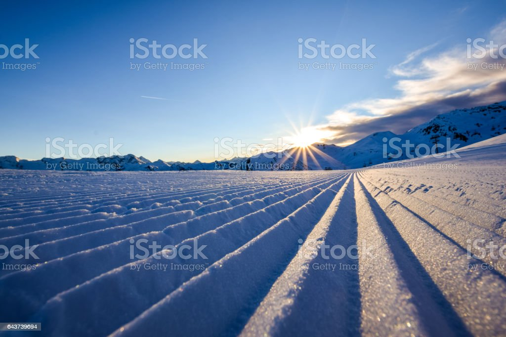 Close up of a freshly prepared skiing slope in the evening sun in the Zillertal skiing area in Austria, Europe. The piste is prepared with a snow grooming machine to ensure perfect conditions. stock photo
