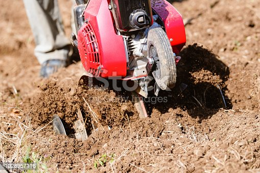 Close up of a rotovator in action in a vegetable garden.