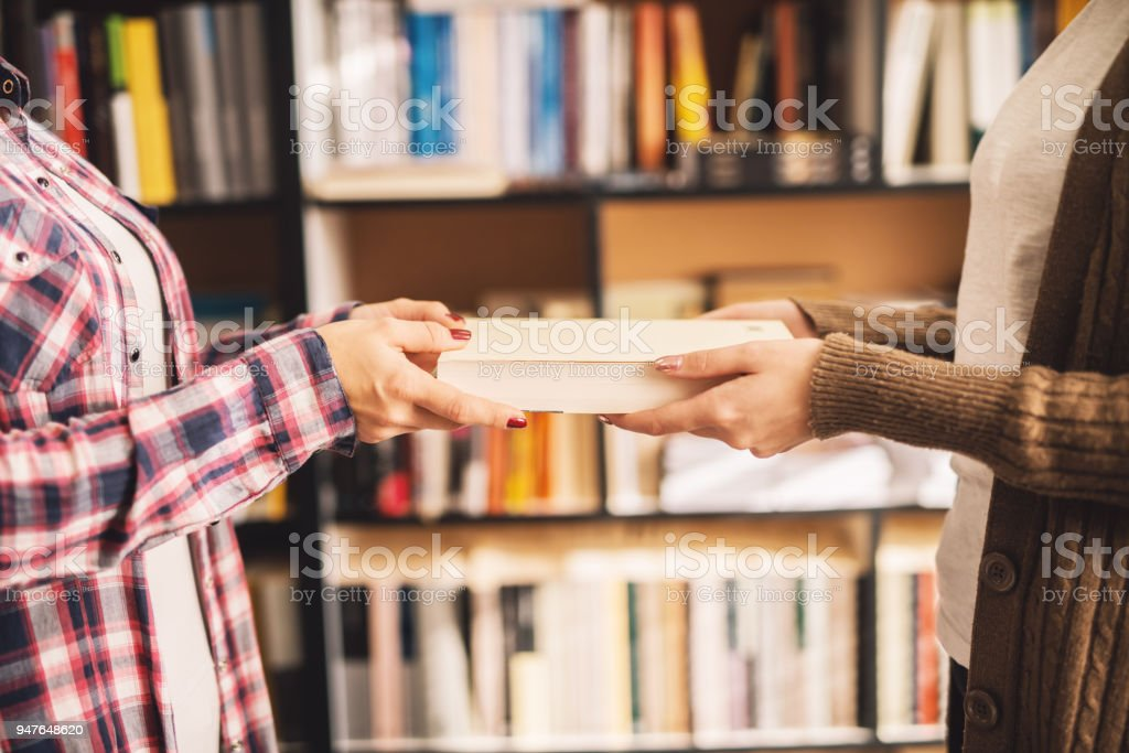 Close up of a girl giving a book to another girl in the library. stock photo
