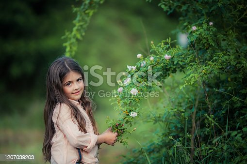 943759290 istock photo Close up of a girl with long brown hair near a green Bush with white flowers 1207039203
