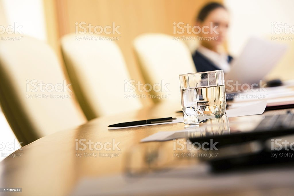 Close up of a glass of water on a conference table Close-up of glass of water on the background of chairs, papers and working woman Arranging Stock Photo