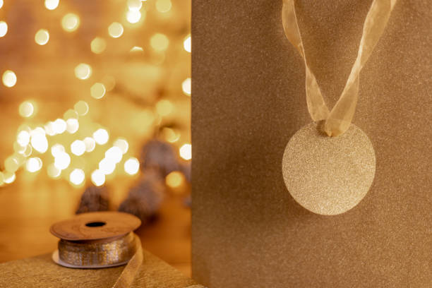 close up of a glitter covered gift bag and tag in gold - christmas stock photos and pictures