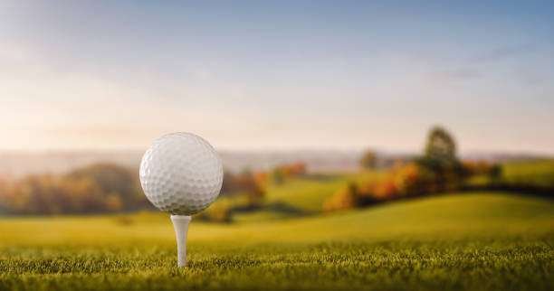 Close up of a golf ball at the golf course tee Close up of a golf ball at the golf course tee with copy space golf ball stock pictures, royalty-free photos & images