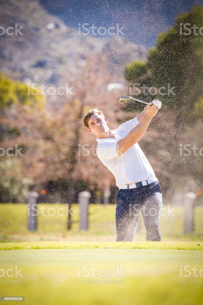 Close up of a golfer making a chip shot onto the green on a golf course in South Africa stock photo