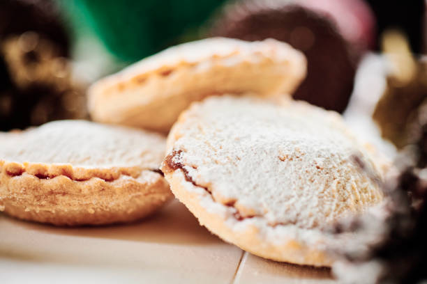 Close up of a group of mince pies on a white table with pine cones and christmas decorations. stock photo