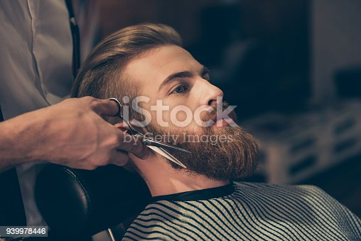 istock Close up of a hairdresser`s work for an attractive young man at the barber shop. He is doing styling of a red beard with scissors 939978446