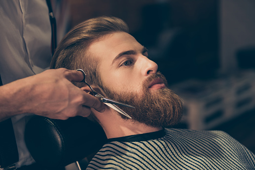 986804130 istock photo Close up of a hairdresser`s work for an attractive young man at the barber shop. He is doing styling of a red beard with scissors 939978446
