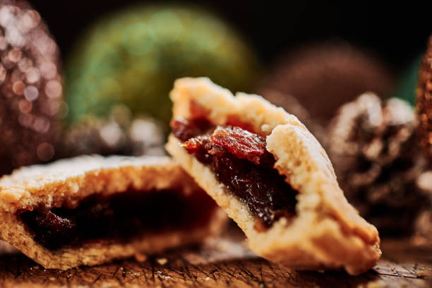 Close up of a halved Mince Pie on a dark rustic wooden surface with pine cones and christmas decorations. stock photo