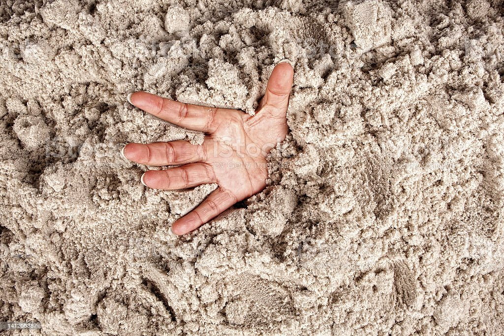 Close up of a hand coming out of deep sand stock photo