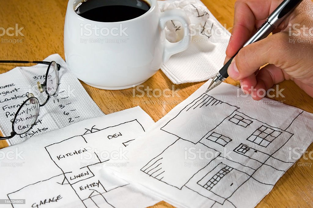 Close up of a hand drawing a house on a napkin  royalty-free stock photo
