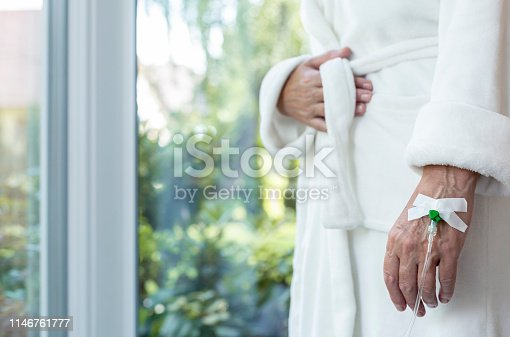 928968772 istock photo Close up of a hand with drip, sick elder patient after chemotherapy in medical center 1146761777