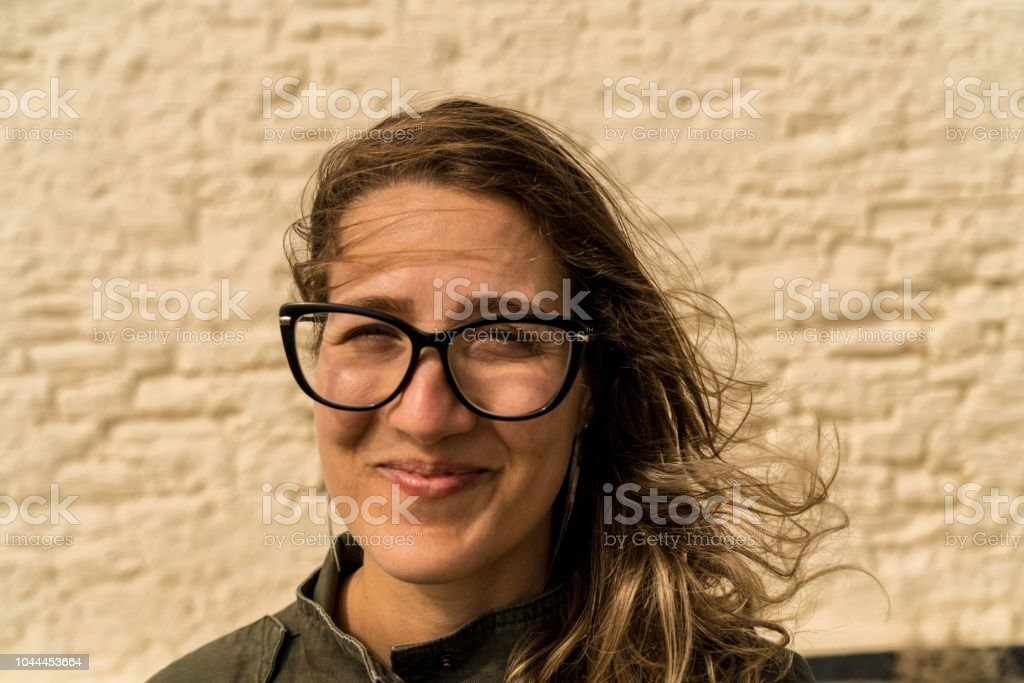 Close up of a Happy smiling girl wearing glasses with the wind messing up her hair royalty-free stock photo