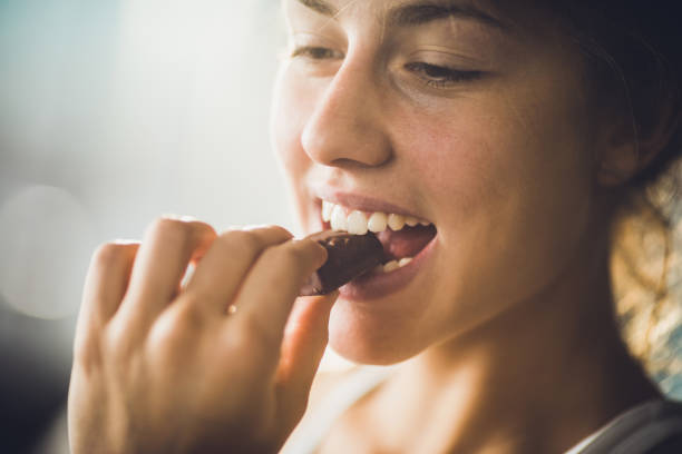 close up of a happy woman eating chocolate. - enjoyment stock pictures, royalty-free photos & images