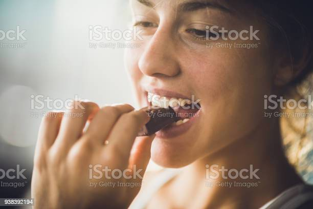 Close up of young beautiful woman biting chocolate candy.