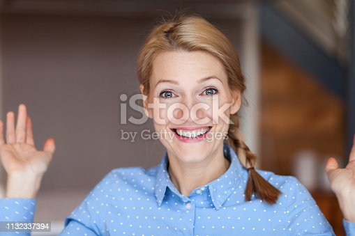 istock Close up of a happy young woman who has a braid. Hands up. Asking. 1132337394