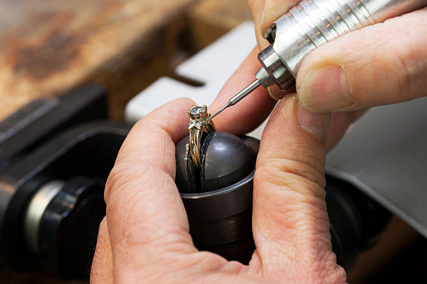 close up of a jeweler's hands doing a repair - diamond ring hand stock photos and pictures