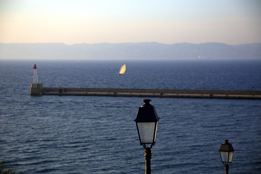 Close up of a lamppost, near the sea, with the background of the pier and a sailing boat, Parc National des Calanques, Marseille, France