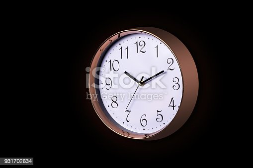 812823858istockphoto Close up of a Large Decorative ticking wall clock in metallic rose gold color and white face, accurate time as it is fitted with a quartz, Isolated object on black background 931702634