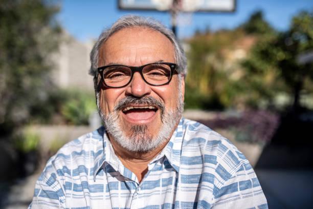 Nahaufnahme eines lateinischen Mannes, der draußen steht und auf die Kamera schaut – Foto