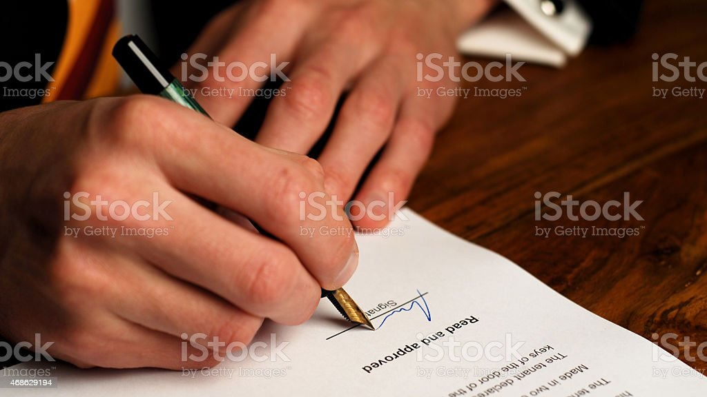 Close up of a lawyer signing a contract stock photo