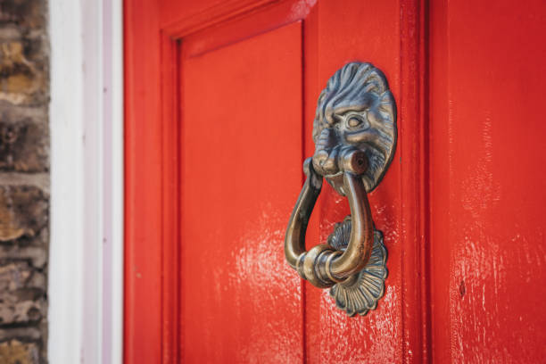 밝은 붉은 도어에는 사자의 머리 문 두 들기는 사람의 닫습니다. - 노커 뉴스 사진 이미지