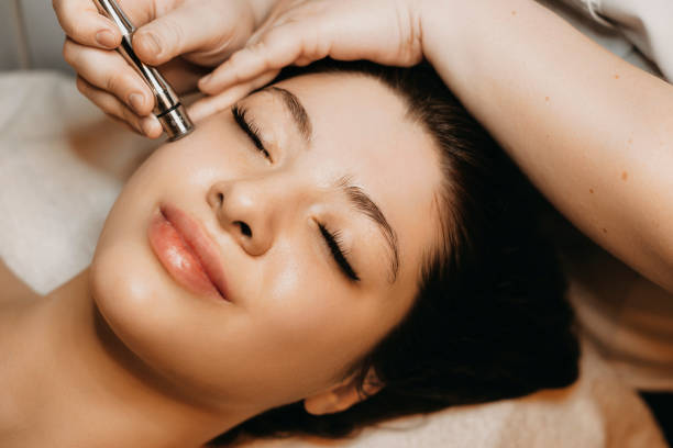 Close up of a lovely caucasian woman having microdermabrasion non invasive therapy with derma pen in a wellness center. stock photo
