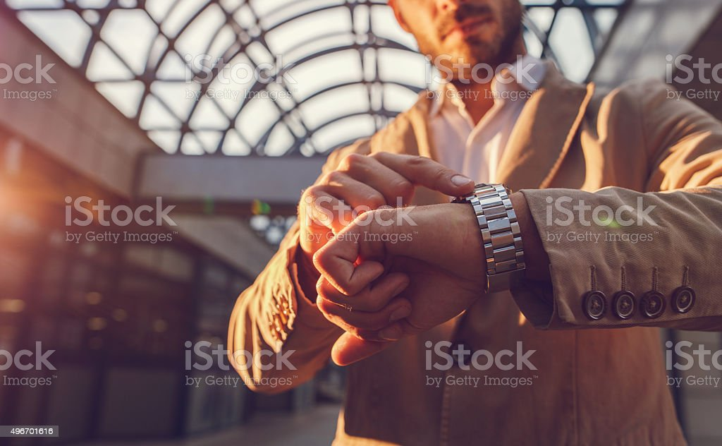 Close up of a man checking the time on wristwatch. stock photo