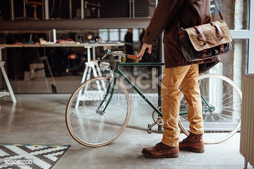 Close up of a man entering office with bicycle