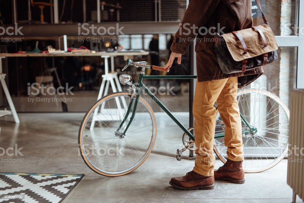 Close up of a man entering office with bicycle stock photo