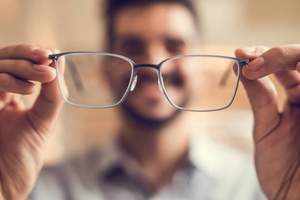 close up of a man holding eyeglasses before trying them on. - optometrist stock pictures, royalty-free photos & images