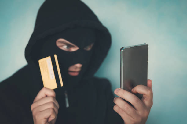 Close up of a man in robbery mask and hood holding the credit card and looking at the smartphone screen. Male criminal arranges a financial affair with mobile and credit card. Network fraud dangers stock photo